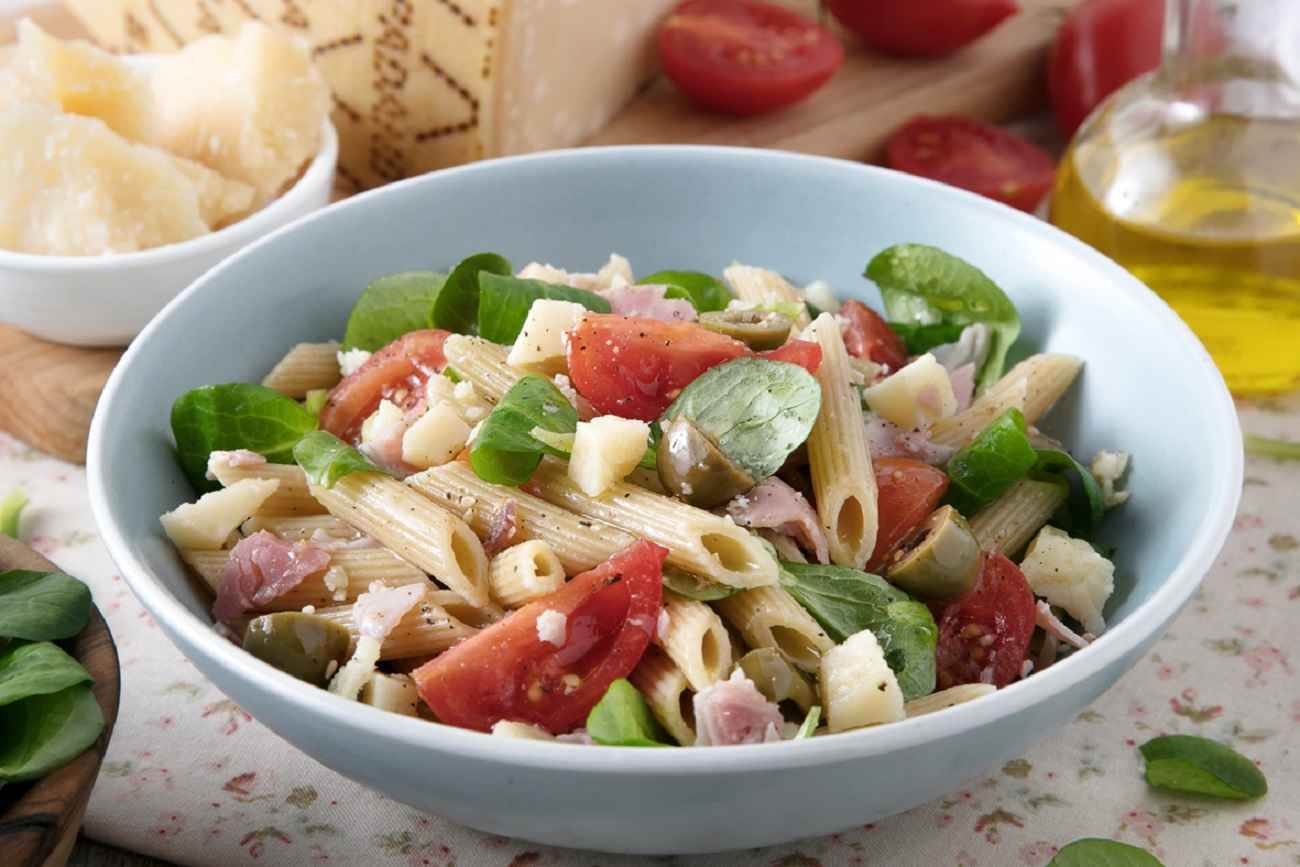 Cold pasta salad with cherry tomatoes, green olives, ham, lamb's lettuce and Grana Padano