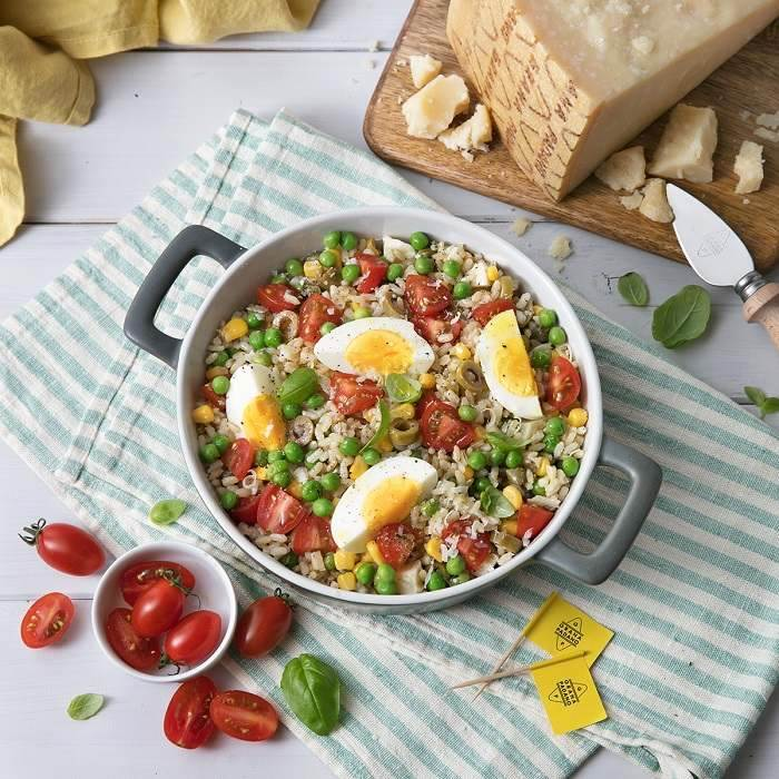 Brown rice salad with peas, tomatoes, hard-boiled eggs, green olives, corn, basil and Grana Padano PDO
