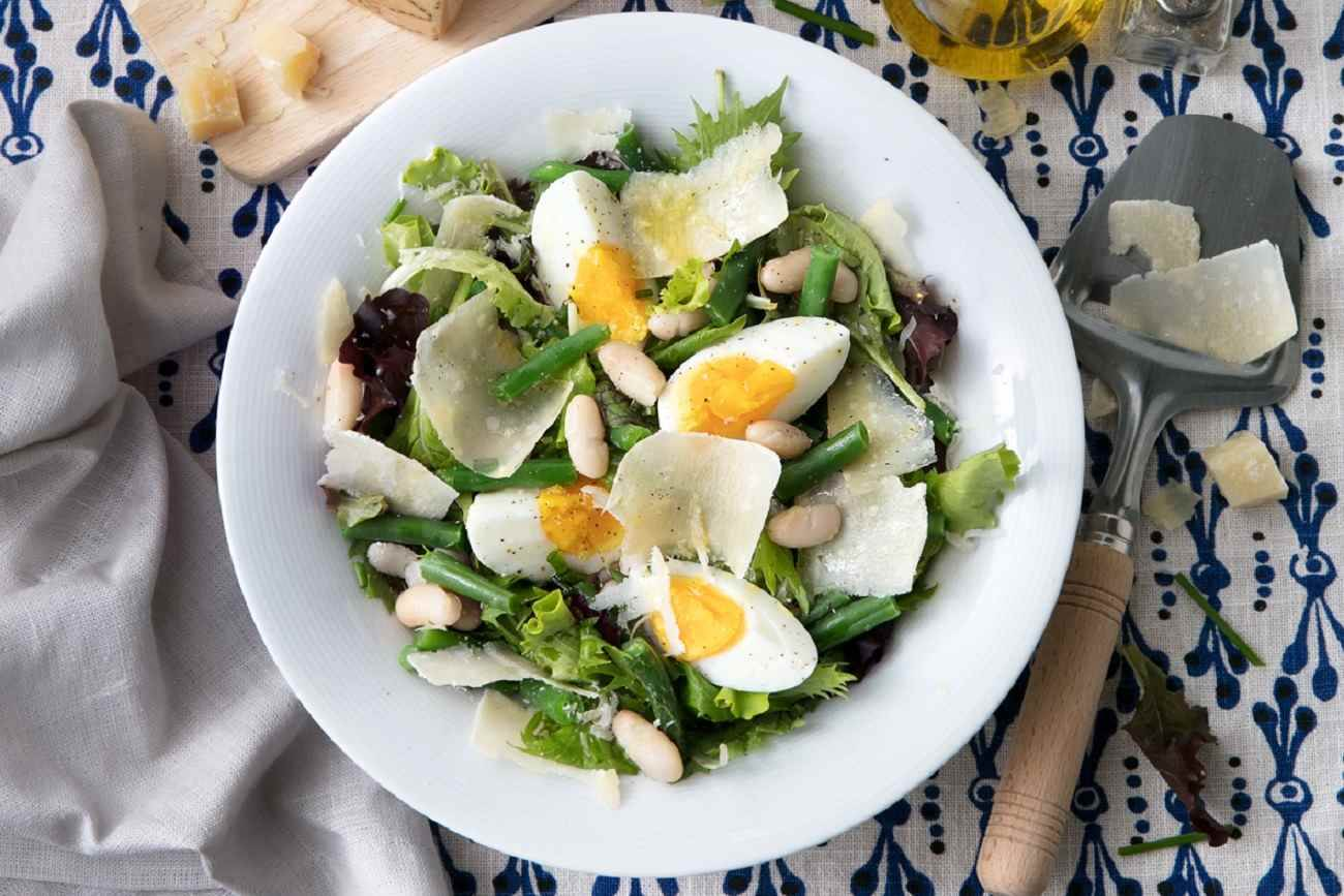 Salad with mixed greens, cannellini beans, green beans, hard-boiled eggs, chives and Grana Padano