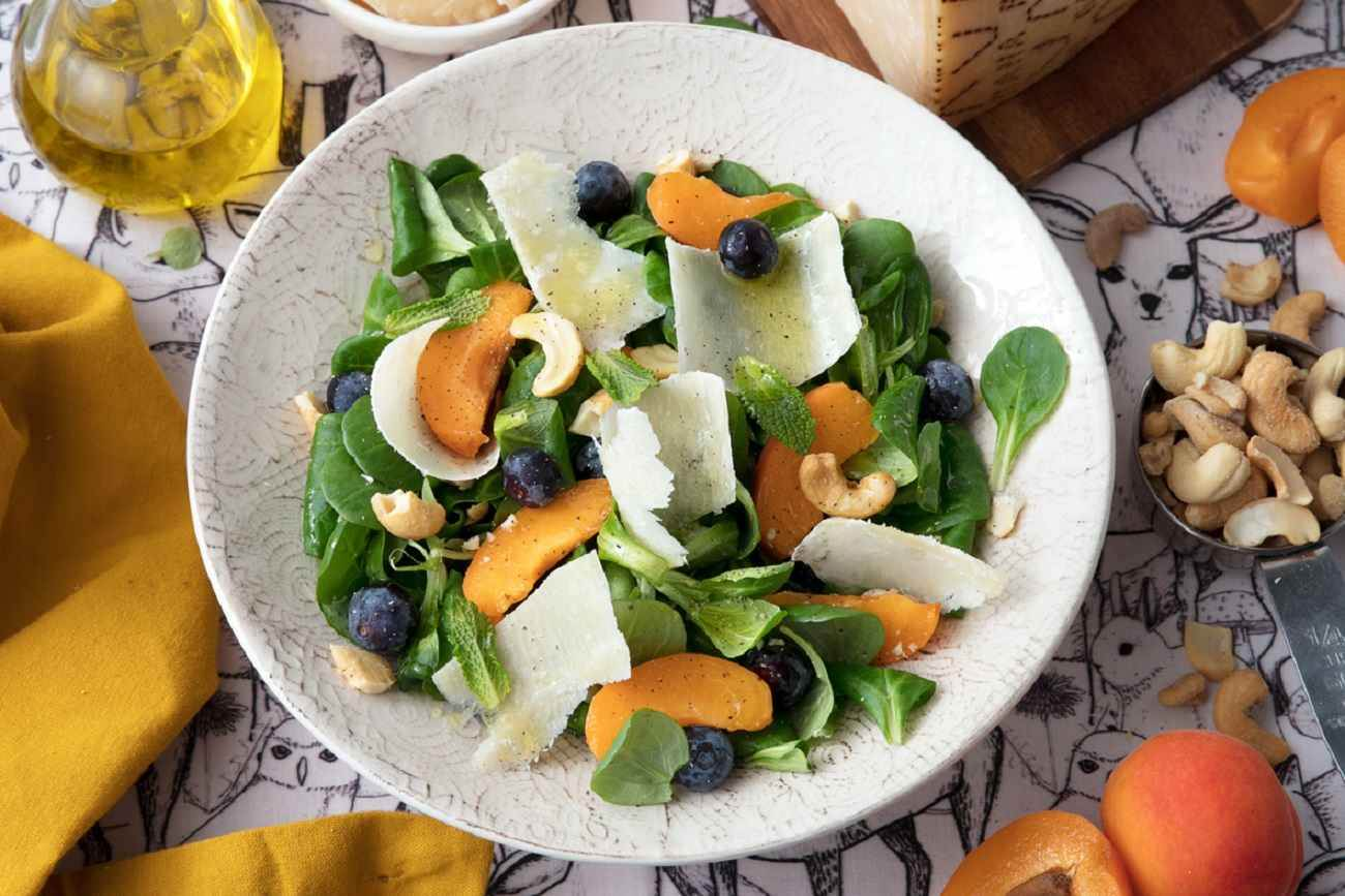 Salad with lamb's lettuce, apricots, cashews, blueberries, mint and shavings of Grana Padano