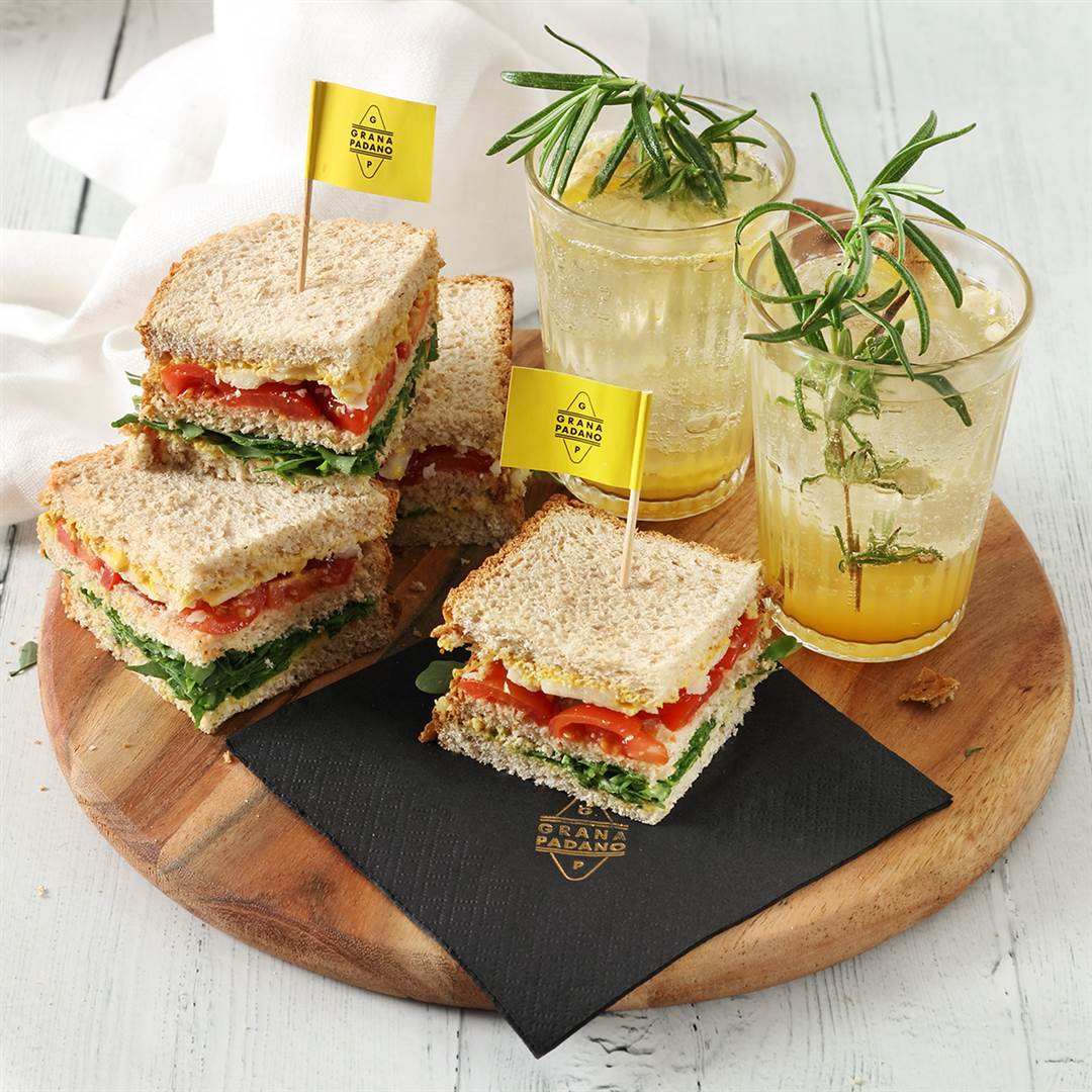 Pineapple juice, tonic water, ginger and rosemary mocktail, mini whole wheat sandwiches with tomato, rocket, mustard and shavings of Grana Padano