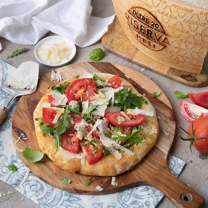 White pizza with fresh tomatoes, rocket and shavings of Grana Padano Riserva