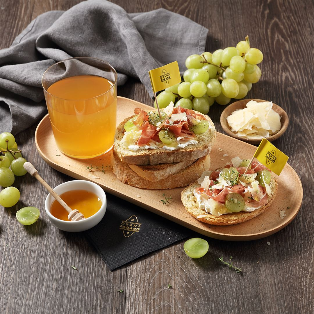 Apple Cider served with Canapes of Homestyle Bread served with White Grapes, Prosciutto, Honey and Shavings of Grana Padano