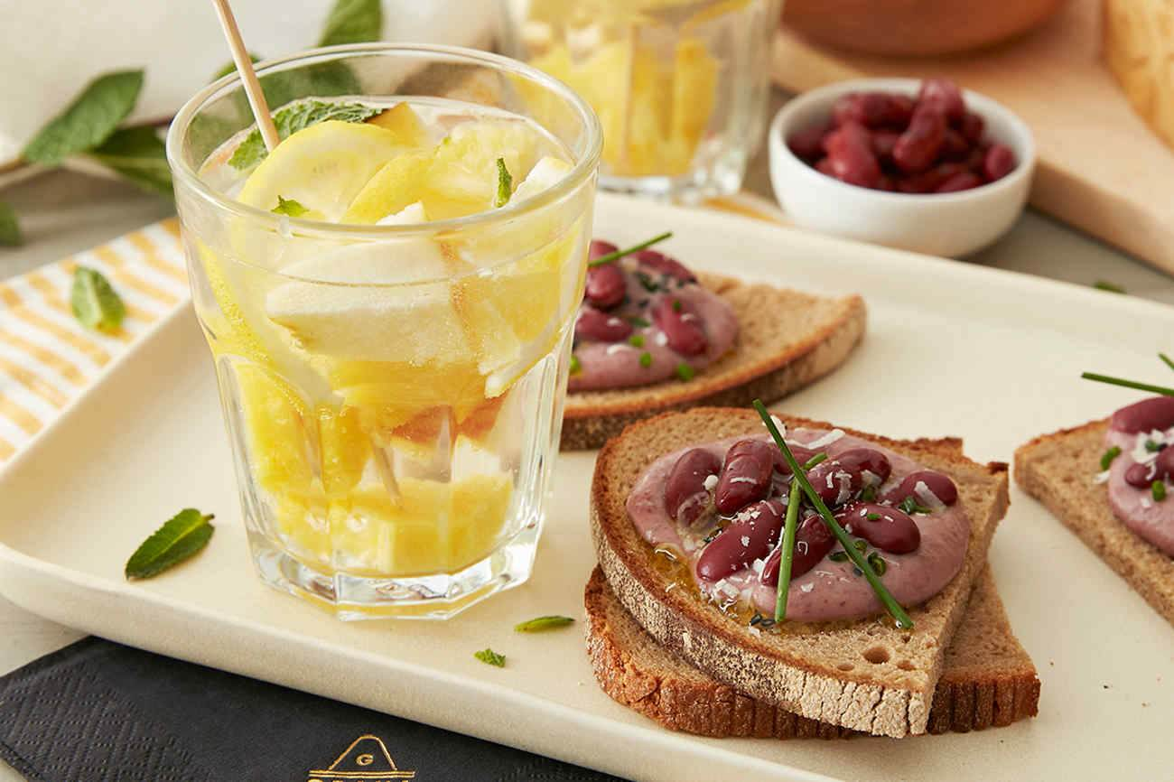 Non-alcoholic White Sangria and Toasted Rye Bread with Hummus and Grana Padano