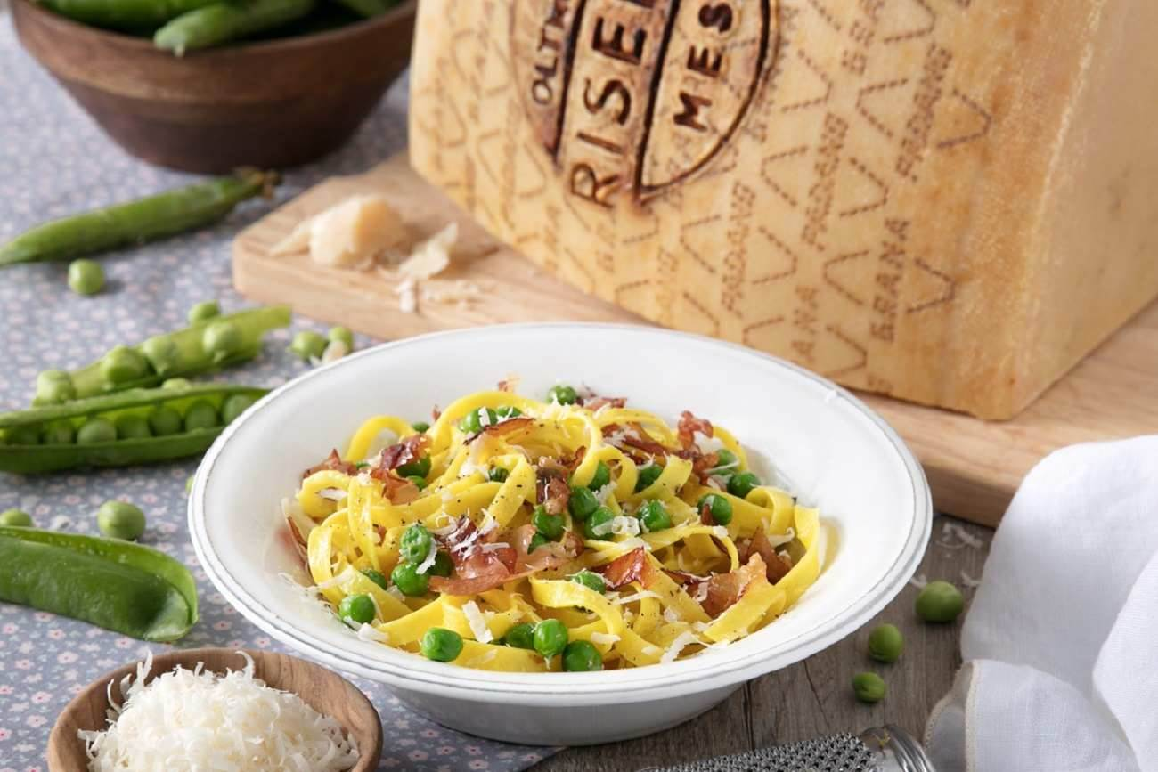 Tagliatelle with fresh peas, speck and shavings of Grana Padano Riserva
