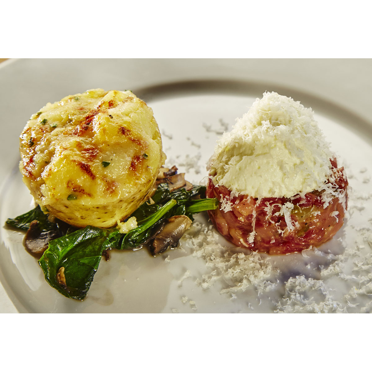 Stuffed potatoes with grappa, Grana Padano mousse, spinach and beef tartare